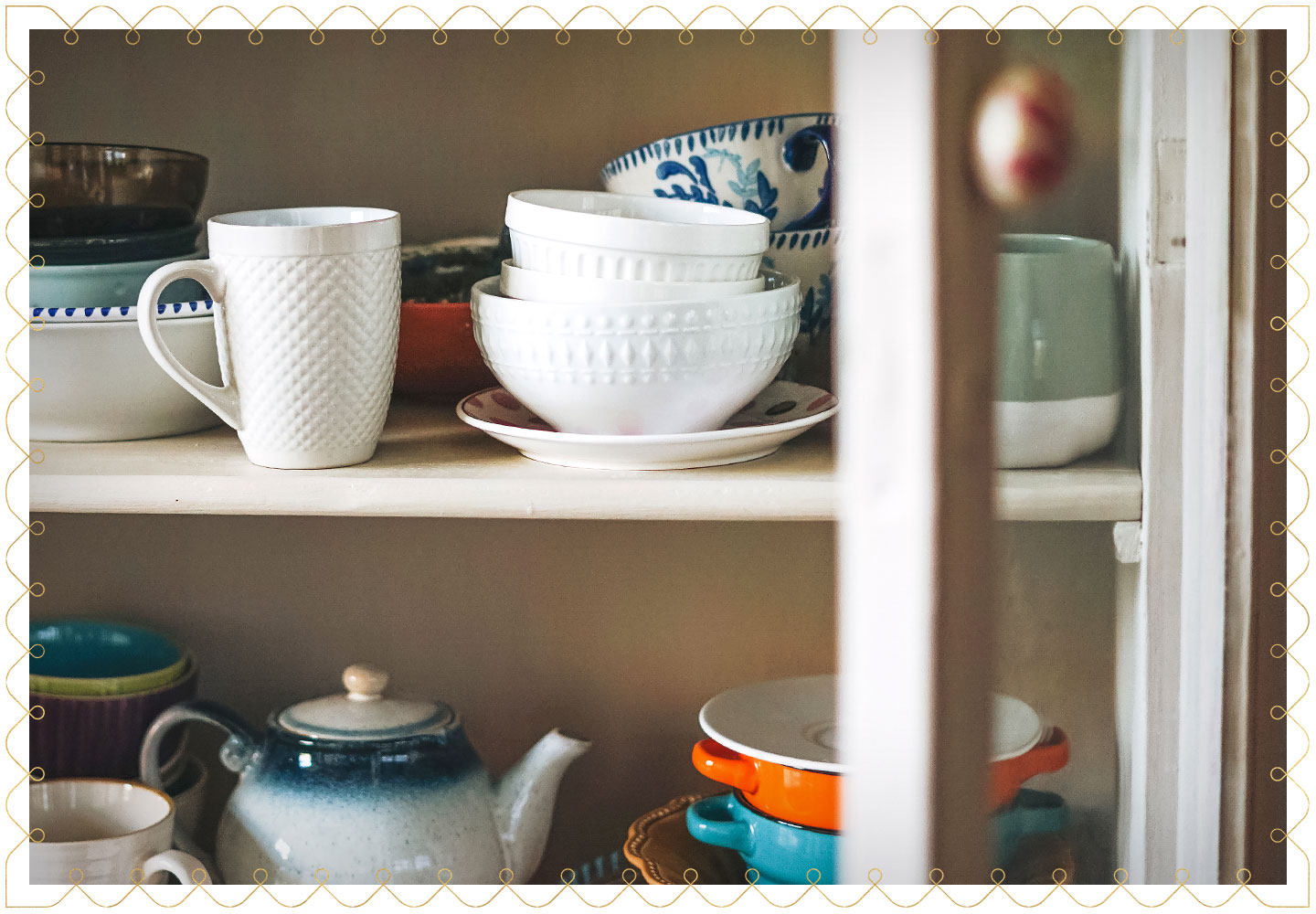 porcelain dishes like mugs, bowls and plates in a cabinet with an open glass door