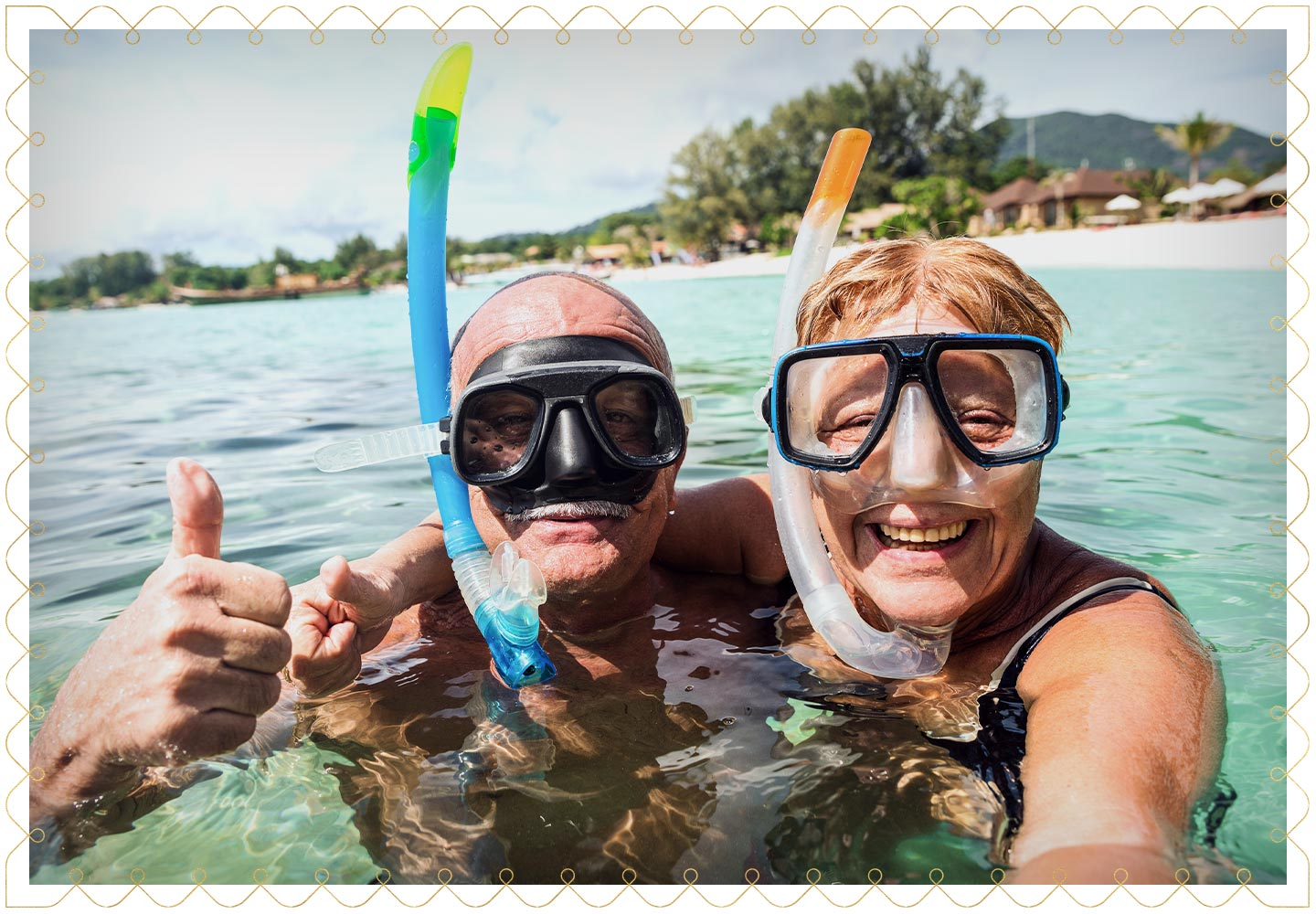 happy middle-aged couple with snorkels and goggles on taking a selfie in the water at a tropical vacation place