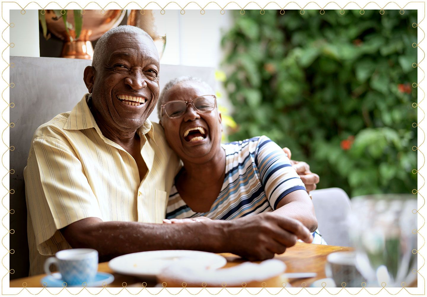 elderly couple laughing at the camera while hugging each other at a table