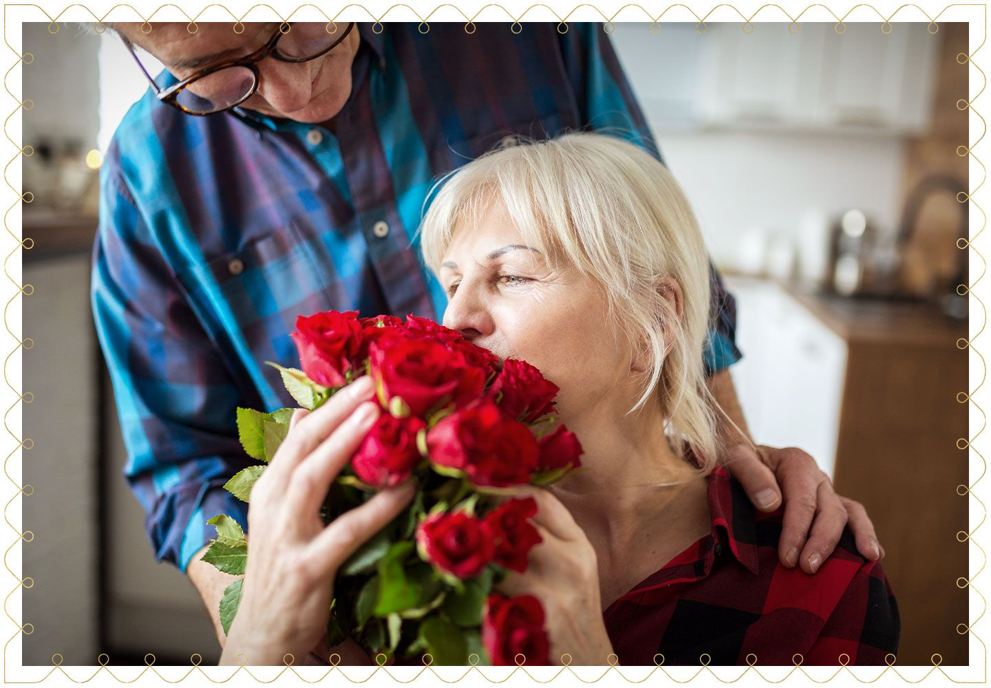 older woman smelling a bouquet of red roses while her partner leans over her shoulder smiling down at her