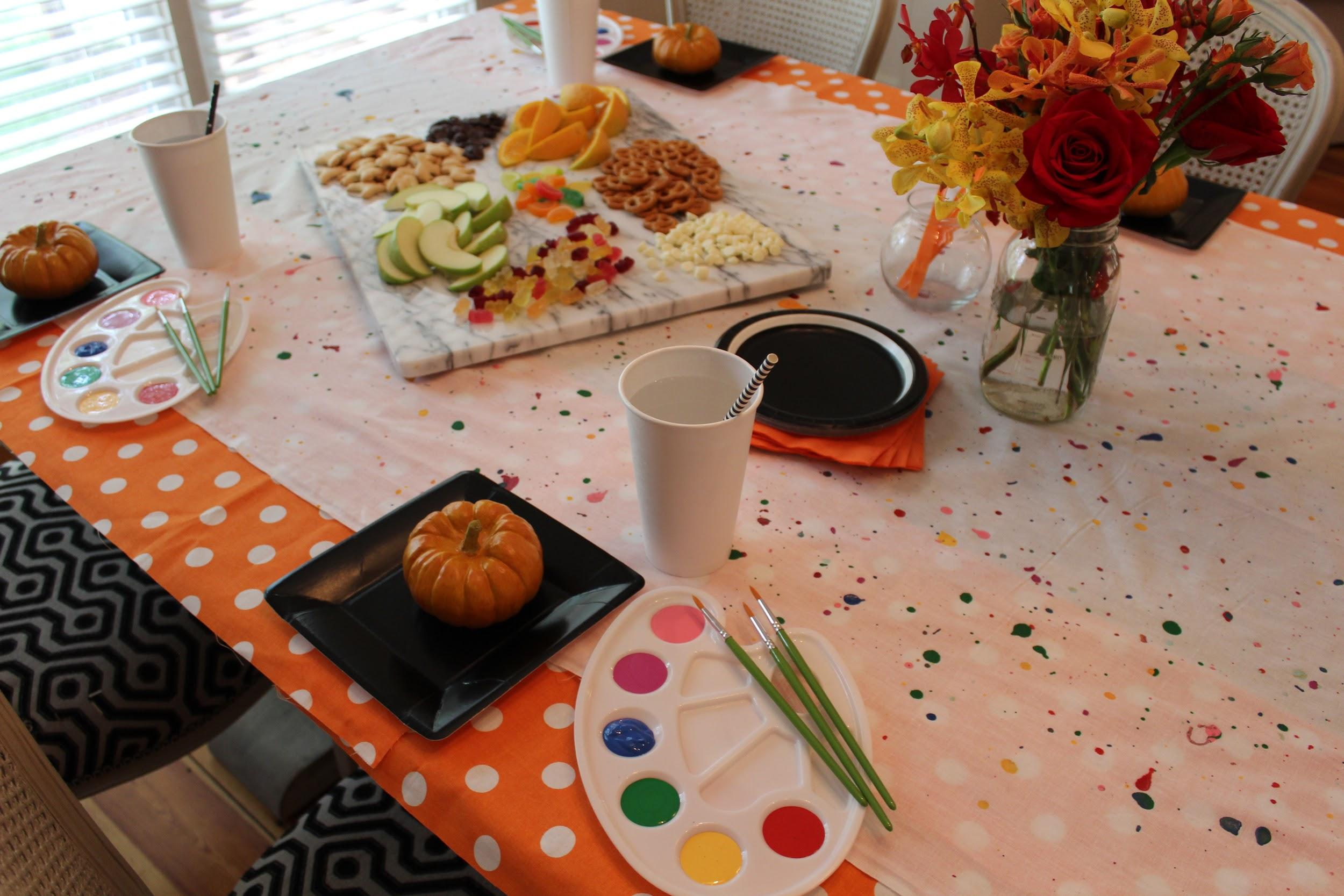 autumn party food and flowers on a table with paint