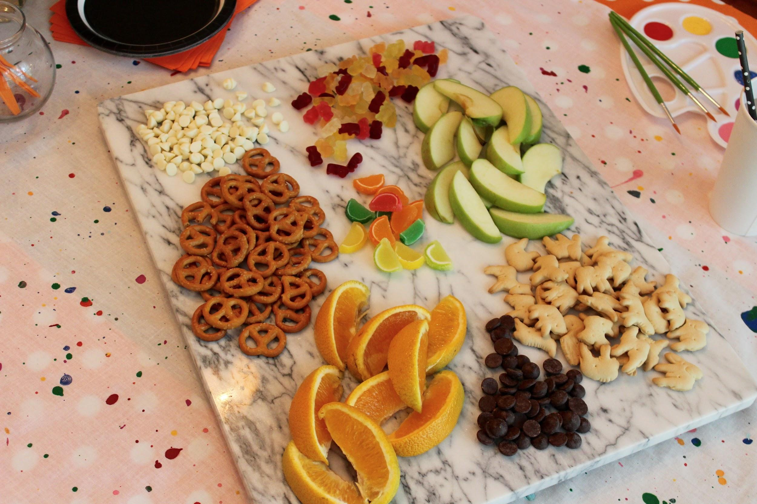 autumn party snacks candy oranges apples chocolate chips and pretzels