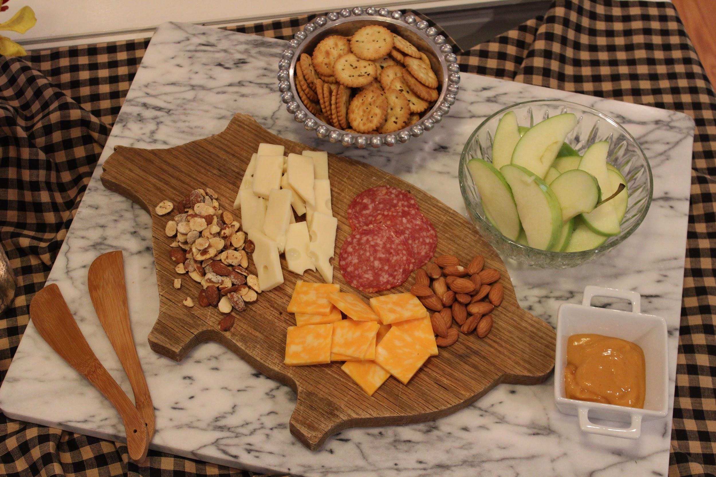 pig shaped cutting board nuts and cheese crackers and apples