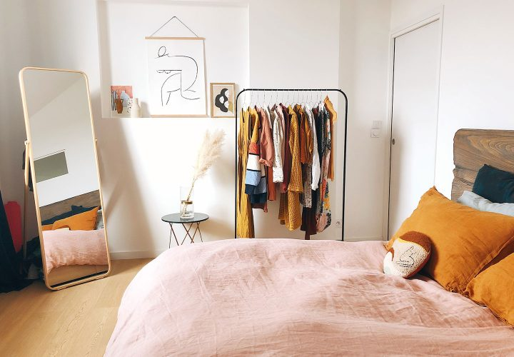 pink and orange bedroom with clothes and mirror.