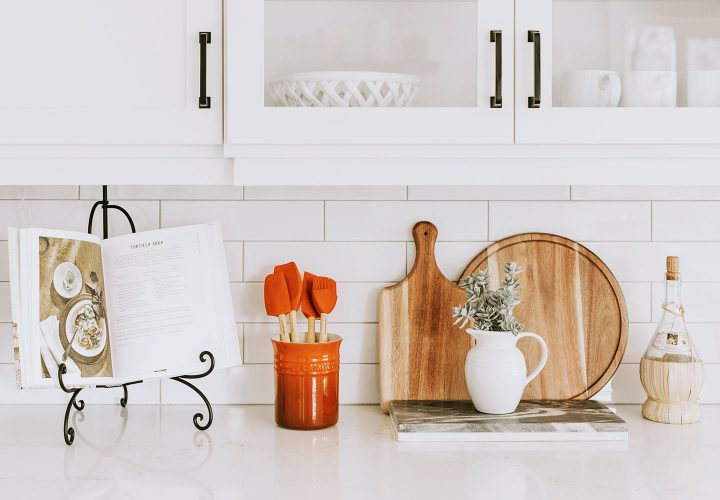 white kitchen with cook book and plant.