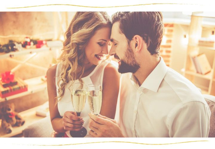 couple facing eachother and smiling with champagne.