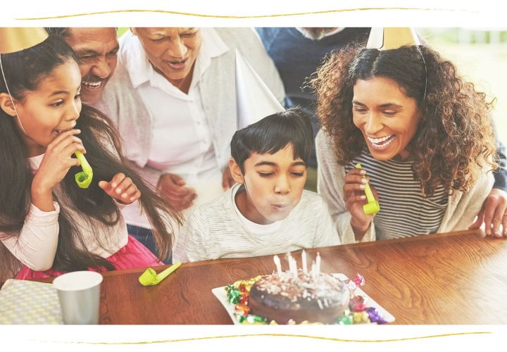 young boy with birthday hat blowing out candles on cake.