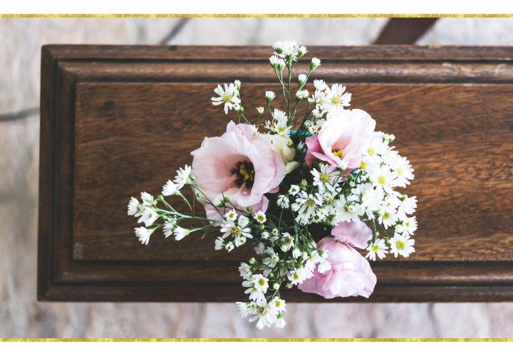 pink flower bouquet laying on coffin.