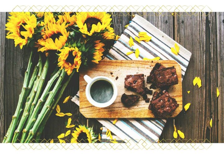 tray with coffee and brownie on table next to sunflowers.