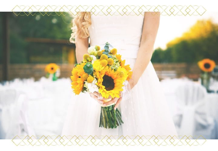 bride in white dress holding bouquet of sunflowers.