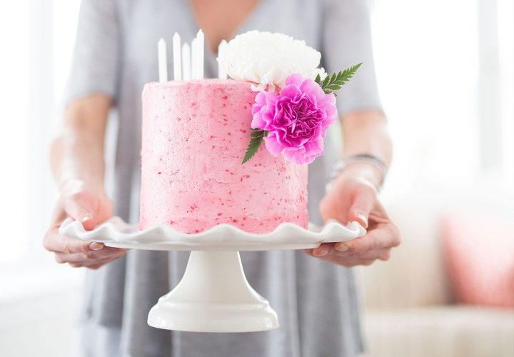 woman holding pink birthday cake on white cake stand.
