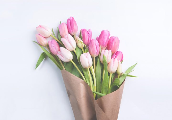 pink tulips wrapped in brown paper.