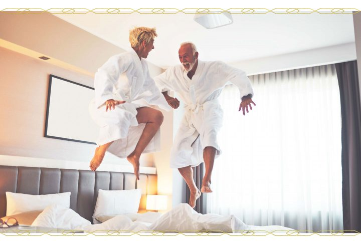 couple holding hands and jumping on the bed.