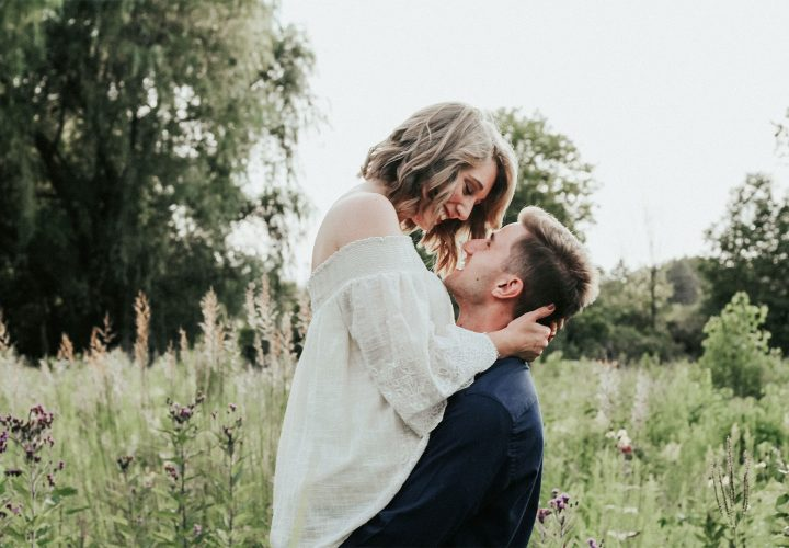 woman embracing man in a field of flowers