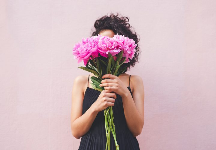 Woman holding flowers in front of face