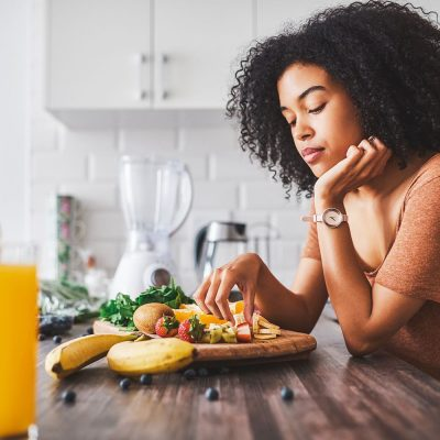 young woman picking at her breakfast