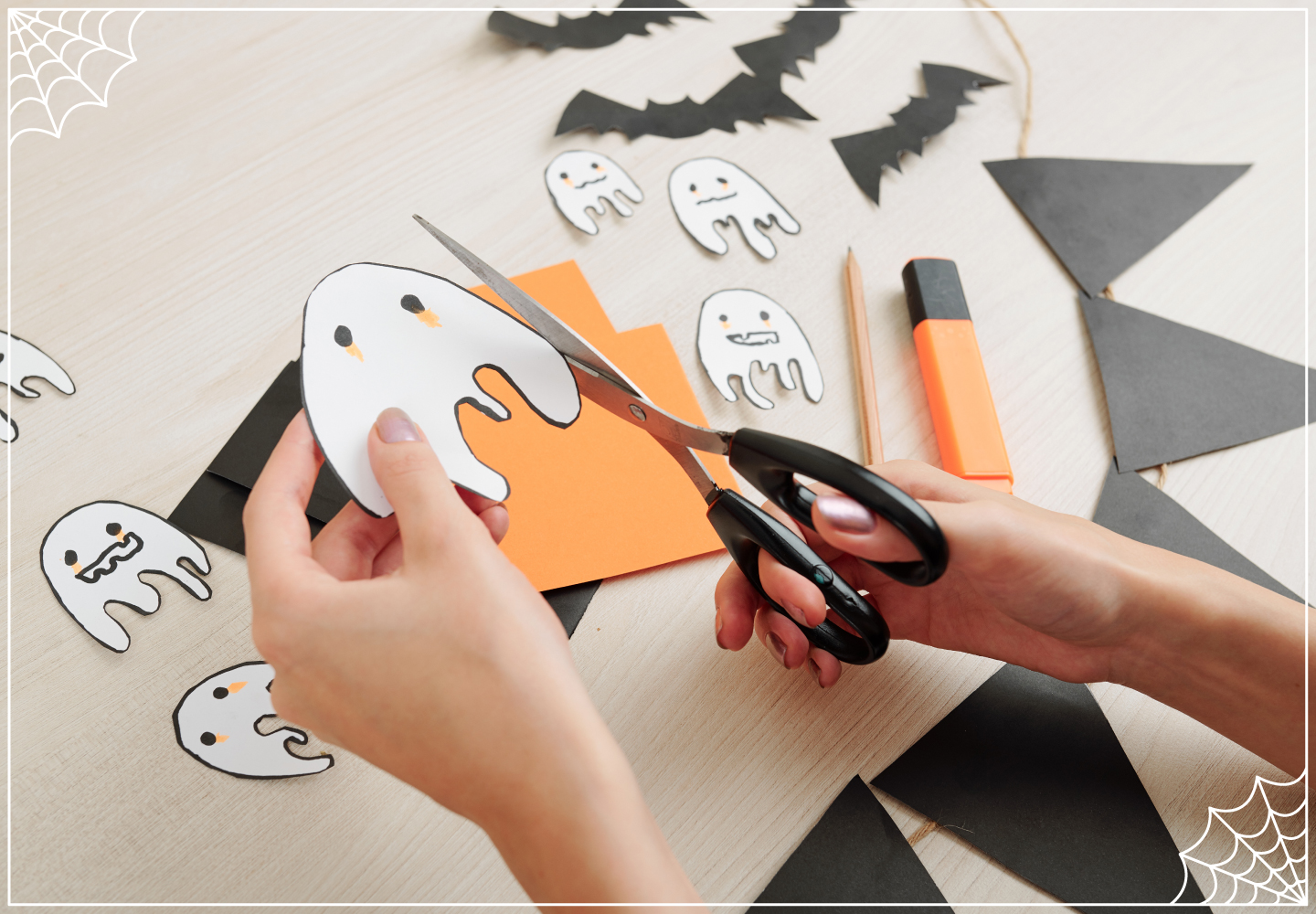 Halloween crafts, hands cutting out a paper ghost with scissors