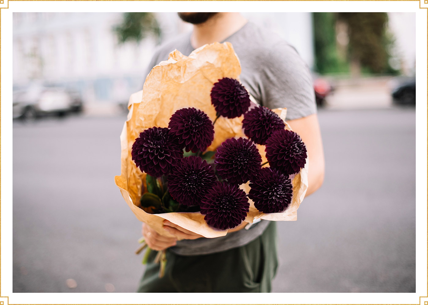man holding a bouquet of black dahlias