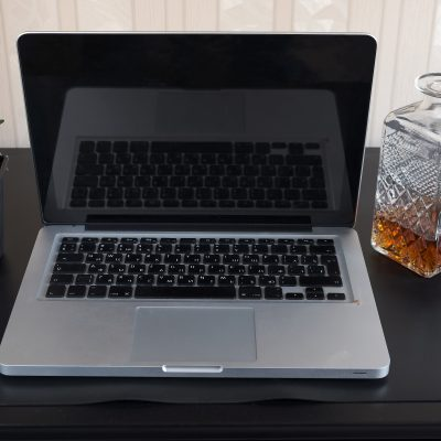desk with laptop and glass of whiskey