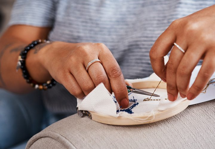 Close up of woman stitching embroidery onto a a piece of cloth in an embroidery hoop.