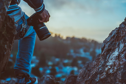 Person holding camera with mountains in the background
