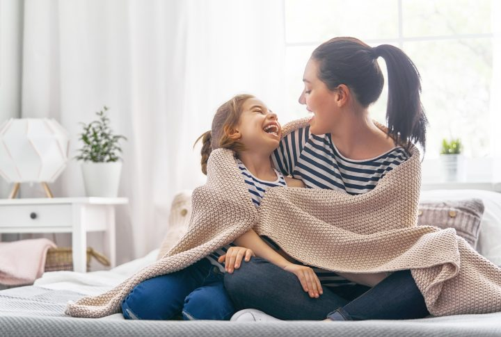 Mom and daughter smiling and laughing together on couch