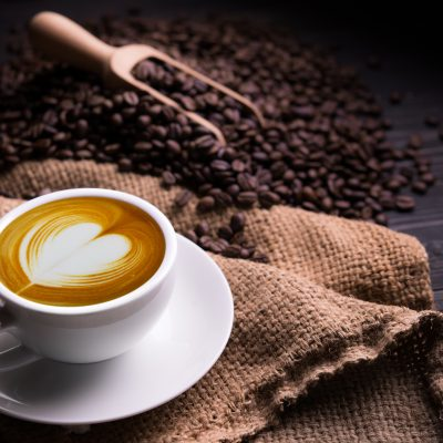 Elegant cup of coffee on dark table with coffee beans