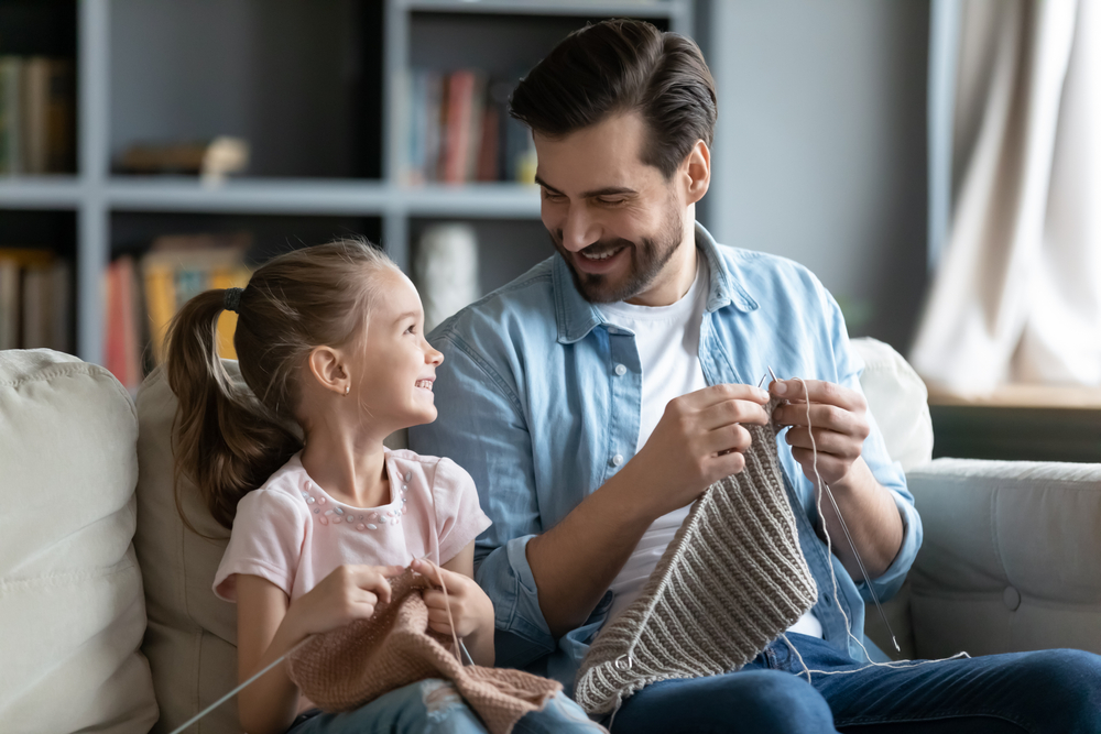 Dad and young daughter on couch knitting and laughing